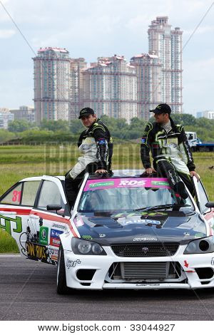 MOSCOW - JUNE 11: G.Hachatryan and G.Stepanyan sit on the car roof at 3-d tour in summer cup of Megafon mitjet race at Moscow racetrack MegaFon Tushino Ring, June 11, 2011, Moscow, Russia.