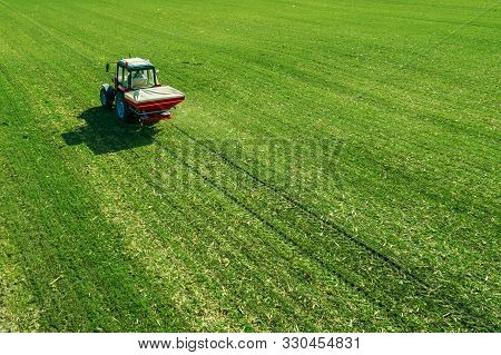 Unrecognizable Farmer In Agricultural Tractor Is Fertilizing Wheat Crop Field With Npk Fertilizers,