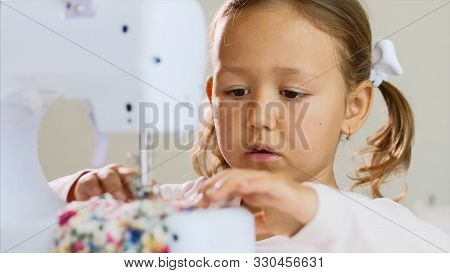 Close-up Of A Little Girl Who Is Making Stiches On Sewing Machine. Portrait.