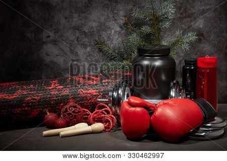 Sports nutrition (supplements), sports equipment, branch of fir,  Christmas ornaments on dark grey background with copy space. Fitness, sport or healthy lifestyle concept. New Year and Christmas.