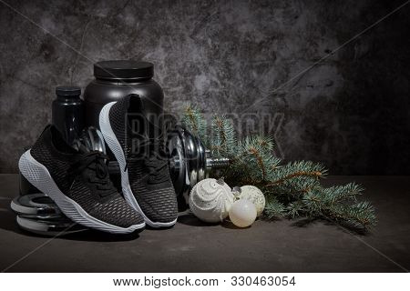 Sports nutrition (supplements), dumbbell, sneakers, branch of fir and Christmas ornaments on dark grey background with copy space. Fitness, sport or healthy lifestyle concept. New Year and Christmas.