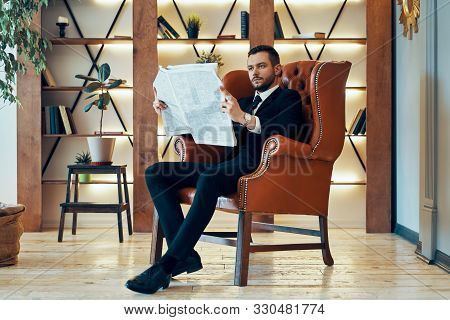 Confident Young Businessman Reading Newspaper And Latest News While Sitting In Armchair In The Morni