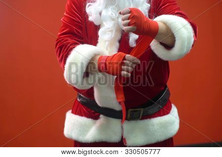 Santa Claus Fighter Kickbox With Red Bandages Against The Background Of A Red Wall