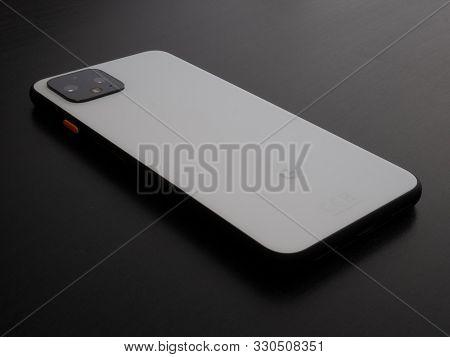 Uk, October 2019: Pixel 4 White Smart Phone Face Down On Dark Wooden Clean Desk