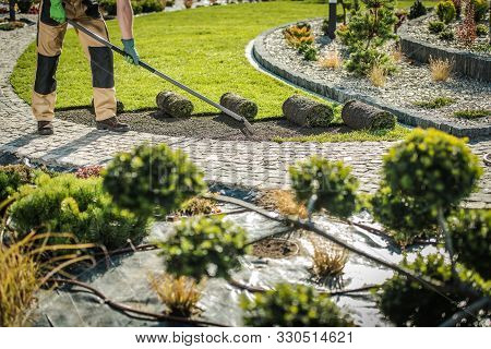 Caucasian Gardener In His 30s Replacing Natural Grass Turfs With New Healthy One. Gardening Job. Lan