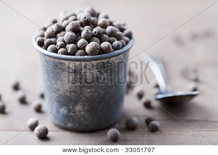 rustic jar full of the herb allspice, also called pimenta or myrtle pepper
