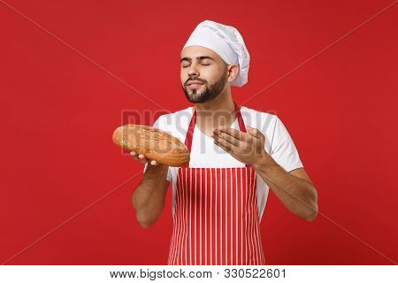Young Bearded Male Chef Cook Or Baker Man In Striped Apron Toque Chefs Hat Isolated On Red Backgroun