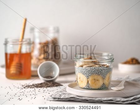 Healthy Breakfast Concept And Idea - Chia Pudding With Organic Banana And Bee Pollen. Glass Jar Chia