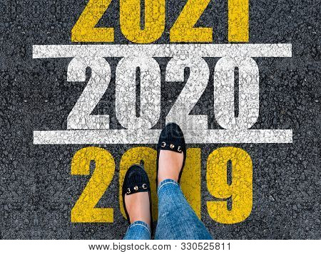 Happy New Year 2020. Lets Start 2020. Woman Legs In Shoes Walks On Asphalt Road Next To Number 2020
