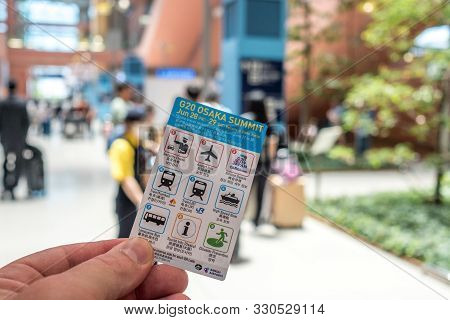 Man Hand Handling G20 Little Card Given To Every Arriving Traveler From International Flight, In Osa