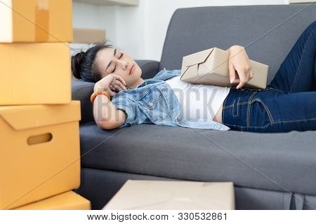 Exhausted, Tired Young Asian Woman Working Overnight And Sleep At Couch With Packing Box Feels Exhau