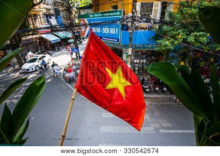 Hanoi, Vietnam - 22nd October 2019: The Red Vietnamese Flag Waves Above The Streets Of Hanoi, The Ca