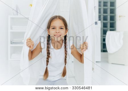 Happy European Girl With Two Plaits, Poses Near Clothes Horse Between White Drying Linen, Poses In W