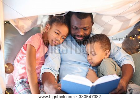 African American man reading bedtime story to his children at home