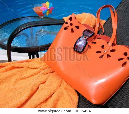 Orange handbag and towel with sunglasses on a chair by the pool