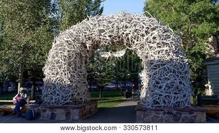 Jackson Hole, Wyoming, Usa -august 17, 2017: A Wide Shot Of A Busker Sitting Beside An Antler Arch I