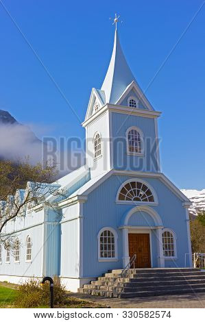 Scenic Wooden Church Painted In Blue Color Against Mountainous Landscape In Northern Iceland. Icelan