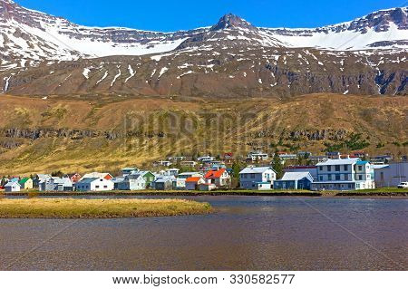 Landscape Of Coastal Town In Northern Iceland During Spring. Mountain Tops Covered In Snow, While Wa