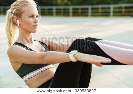 Image of athletic attractive woman wearing tracksuit and earpods doing workout on fitness mat outdoors