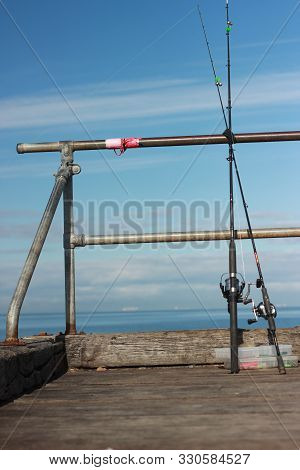 Fishing Paraphernalia Sitting On The Jetty. Ie. Fishing Lines, Floats, Bait And Tools, On A Sunny Af