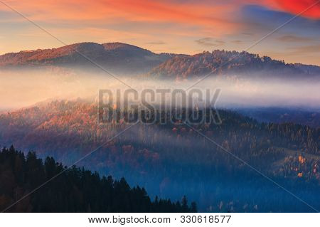 Foggy Dawn In Mountains. Fantastic Nature Scenery In Fall Season. Glowing Mist Above The Hills. Magi