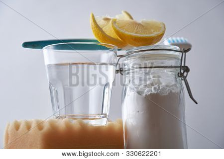 Vinegar, lemons and baking soda with tooth brush on white background. House cleaning