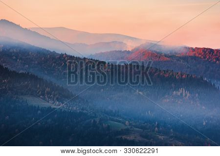 Misty Sunrise  In Mountains. Beautiful Nature Scenery In Autumn. Glowing Fog On Hills. Magic Moment
