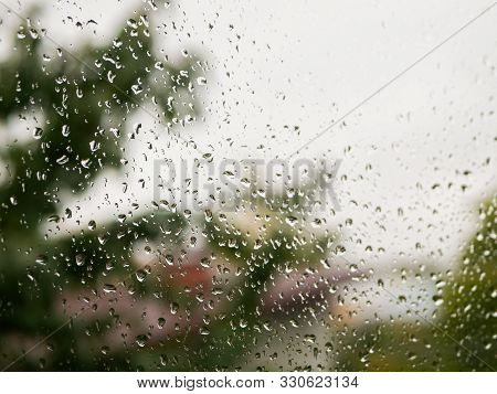 Raindrops On The Glass. Rainy Weather. Against The Background Of A Blurred Background Of Nature. Rai