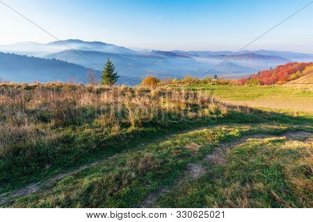 Beautiful Countryside In The Morning. Path Through Meadow In Weathered Grass. Trees On The Hills In