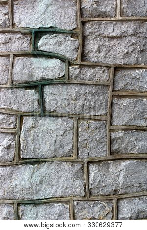 Craftsmanship Can Easily Be Seen In The Cold Cement And Stone Exterior Wall Of Building, With Heavy