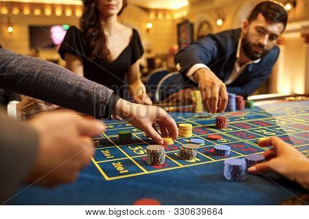 A Group Of People Gamblers Playing Gambling Poker Roulette In A Casino
