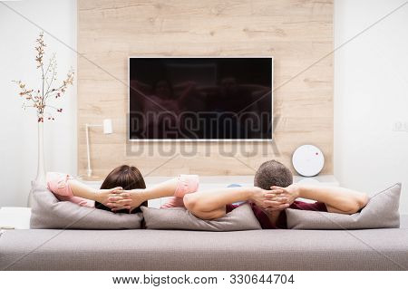 Back View Of Couple Man And Woman Resting In Apartment, Sitting On Sofa Together And Watching Tv