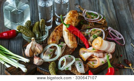 Vodka With Lard, Salted Fish And Vegetables, Sausages On Wooden Background. Alcohol Pure Craft Drink