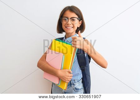 Beautiful student child girl wearing backpack glasses books over isolated white background happy with big smile doing ok sign, thumb up with fingers, excellent sign