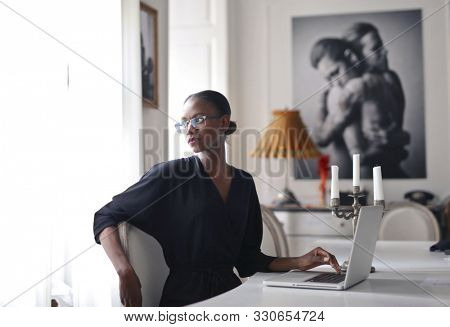 black woman with laptop in a luxury home