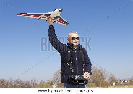 Happy senior RC modeller launching RC plane