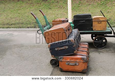 Two Railway Station Luggage Trollies With Cases.