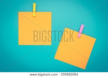 Yellow Sticky Note With Clothespin. Two Orange Stickers On A Blue Bulletin Board. Reminder, Planning