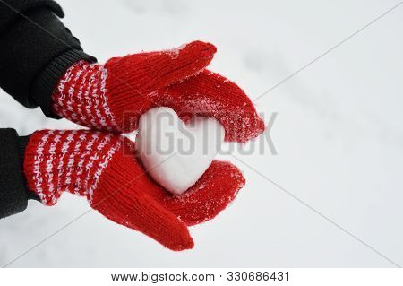 Female Hands In Warm Red Crocheted Mittens With Snowy Heart. White Snow Background. Love Concept. Va