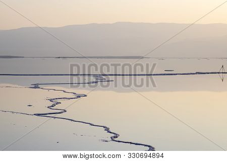 Reflection Of The Jordanian Mountains In The Water Of The Dead Sea With Salt Formations At Dawn. Isr