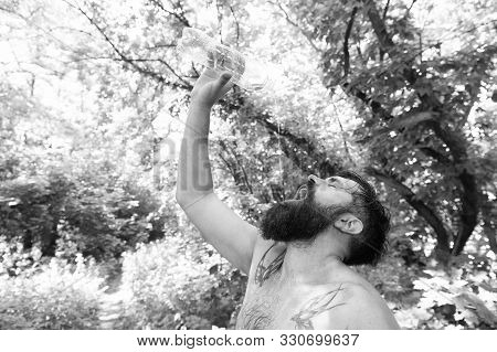Summer heat. Man thirsty sweaty hipster naked in forest. Heat concept. Bearded tattooed guy relax in nature hot summer day. Hipster wet skin and hair survive heat. Vacation resort. Extreme heat. poster