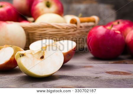 Sliced Apple And Ripe Red Apples On A Wooden Table And In A Basket. Close-up
