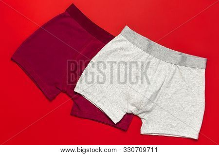 Men's Underwear, Red Burgundy And Gray Underpants On Red Background Flat Lay Top View Copy Space. Fa
