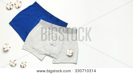 Men's Underwear, Set Of Multi-colored Underpants And Cotton Flowers On White Background Flat Lay Top