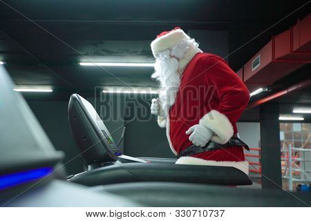 Santa Claus Training At The Gym On Christmas Day. Santa Claus Running In Machine Treadmill At Fitnes