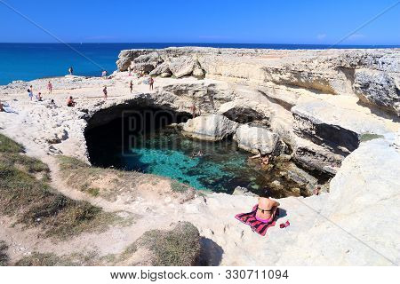 Salento, Italy - June 1, 2017: People Visit Grotta Della Poesia Swimming Hole In Roca, Salento Penin