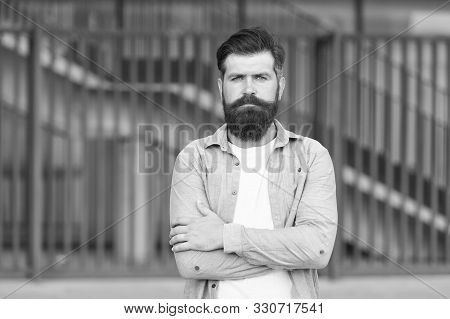 Adding Care To His Mustache. Serious Guy Wearing Beard And Mustache On Urban Background. Bearded Man