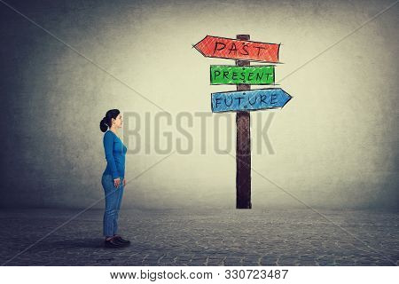 Side View Of Young Woman Standing In Front Of A Signpost With Arrows Shows Past, Present And Future.