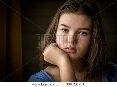 Indoors portrait of a sad pensive teenage girl brunette close-up face. Real people