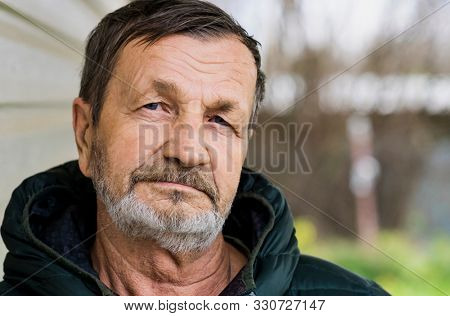 Pensive sad elderly man with a beard and mustache close-up  portrait. Russian village